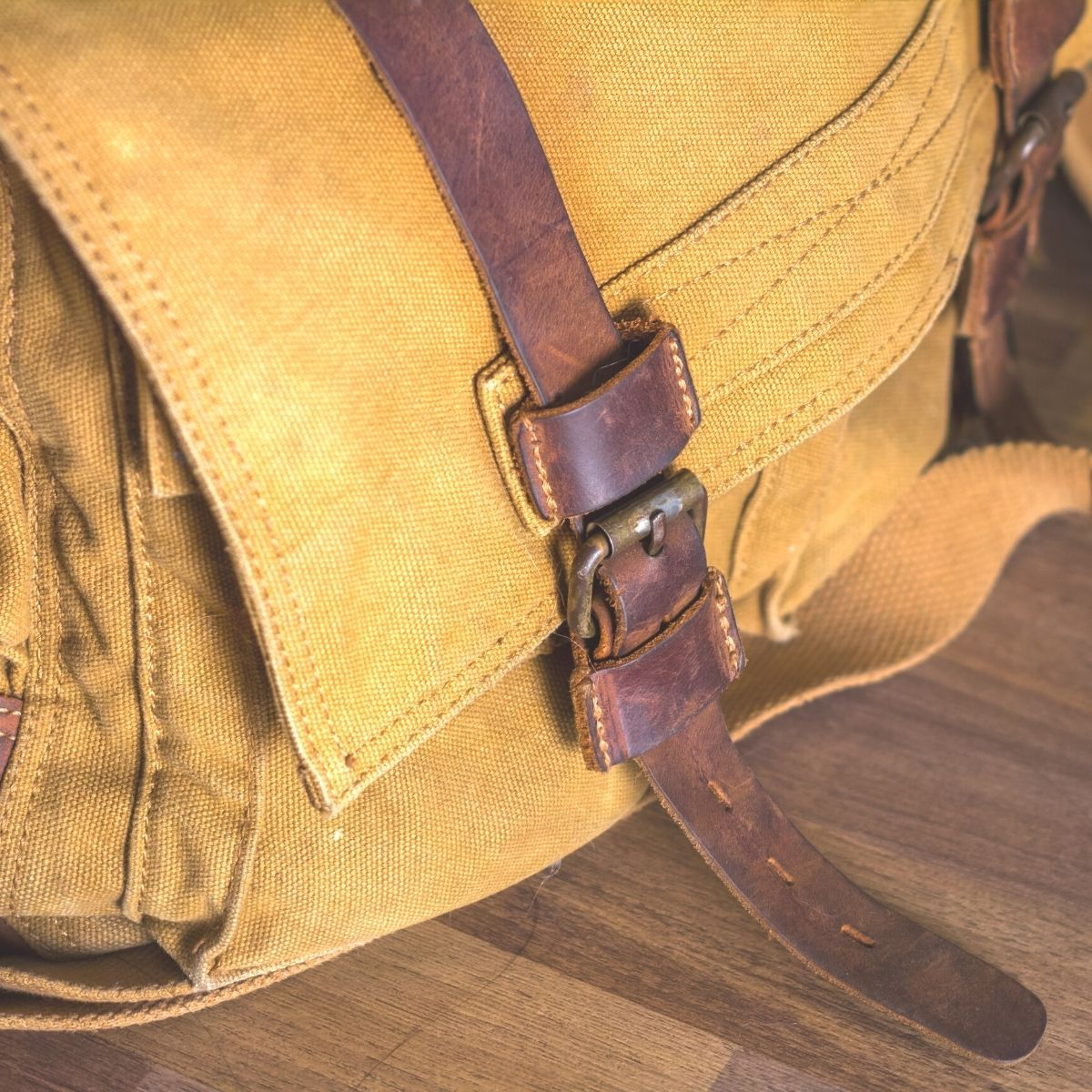a mustard yellow waxed canvas bag with dark brown leather straps is sitting on a wooden table. The picture shows only the left corner front of the bag.