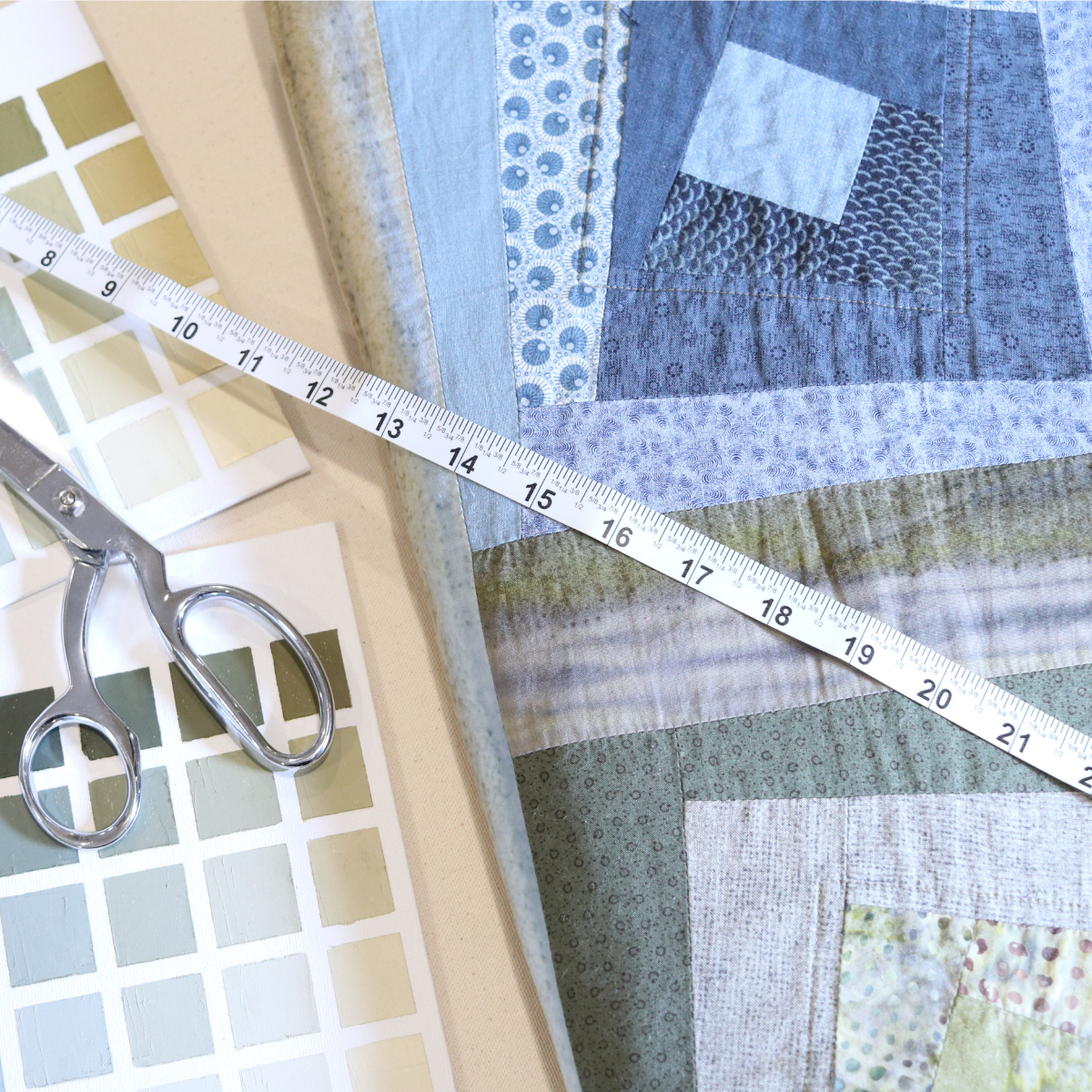a blue and green log cabin quilt resting on a table. a white sewing tape measure laid over the top of it. Sitting next to the quilt is a sew of oil painted color charts that match the quilts color shades of greens and blues. A pair of silver scissors rests onto of the color charts