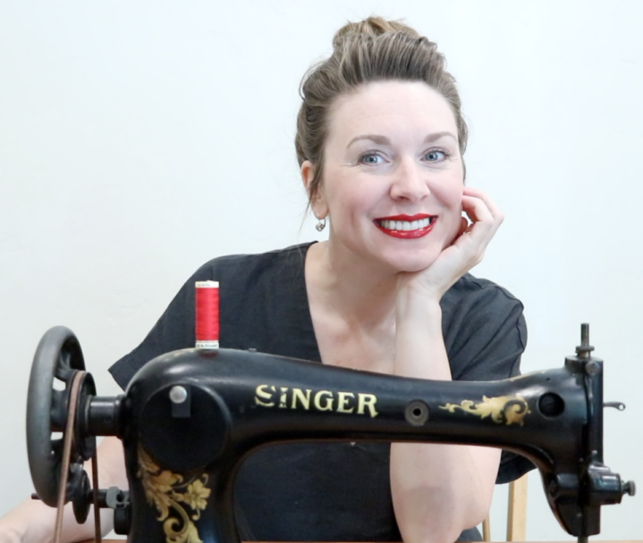 Brie is sitting behind a beautiful black vintage Singer treadle sewing machine. She is wearing a black shirt, her hair is neatly put into a bun and is wearing a bright red Chanel lipstick and smiling at the camera