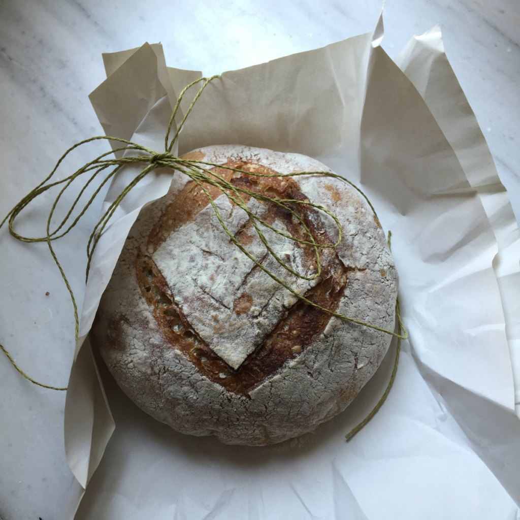 A fresh baked loaf of sourdough bread sitting on a piece of parchment paper. Loaf is being wrapped in paper with a piece of jute twine.