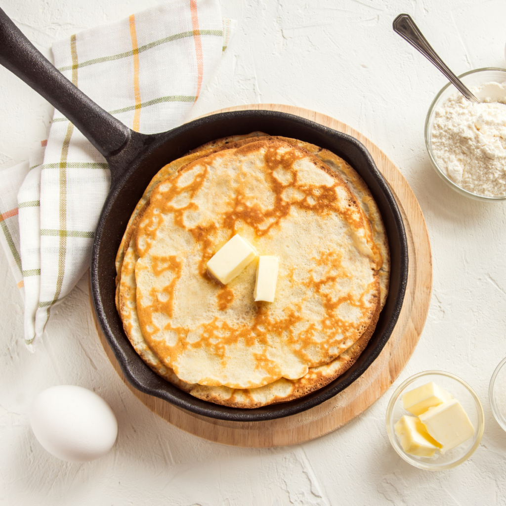 I picture of a black cast iron skillet with a fresher cooked pancake topped with butter inside the skillet. Surrounded on the white table by an egg and ingredients needed to make the pancakes