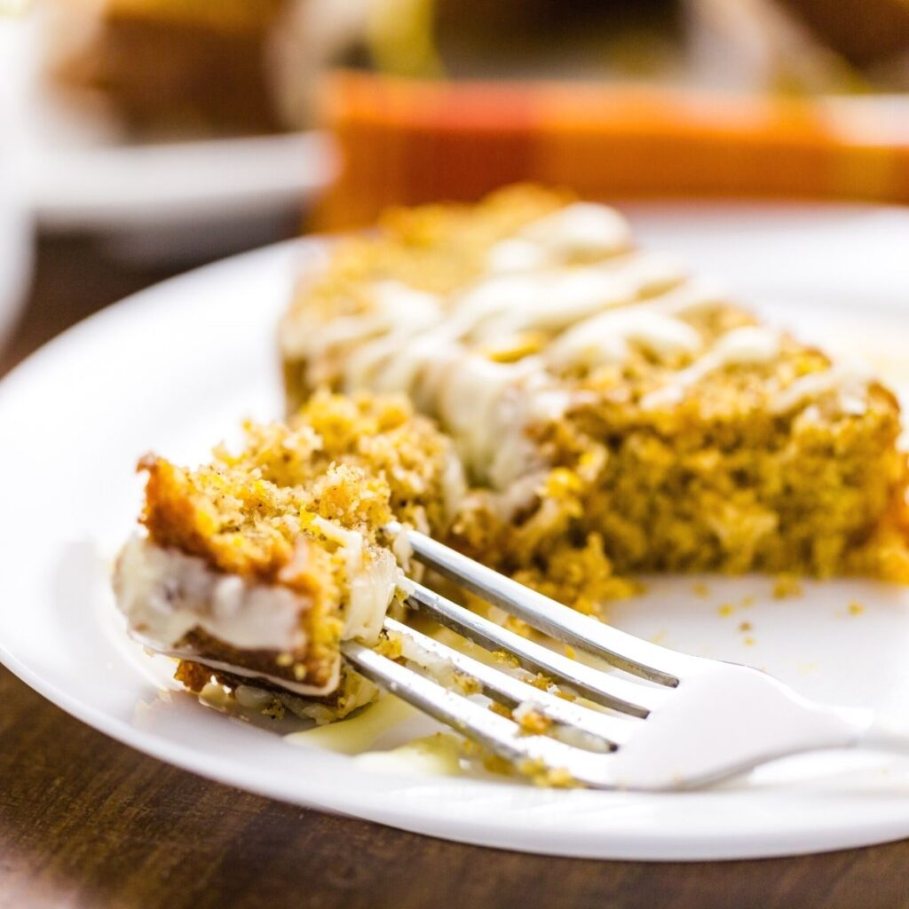 a slice of pumpkin banana bread sits on a white plate. A fork is holding onto a piece of the bread that has a nice drizzle of white frosting on top.