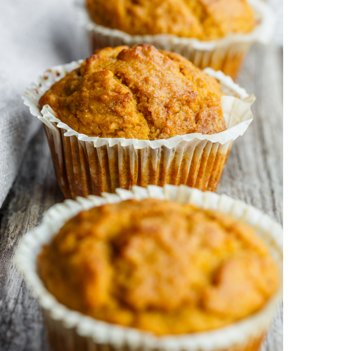an old plank of gray barn wood with three freshly baked sourdough pumpkin banana bread muffins resting neatly on top as they cool off